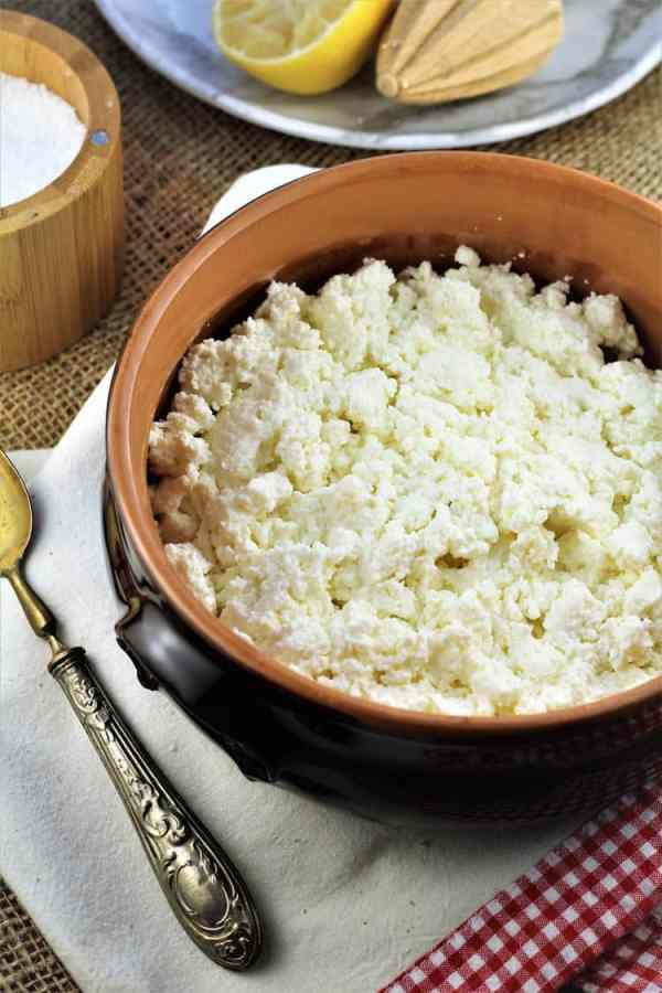 terra cotta bowl with fresh ricotta curds and spoon on side