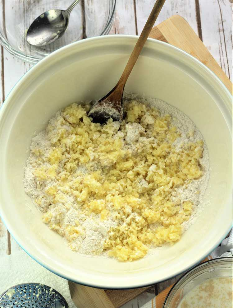 mixing bowl with flour and riced potatoes with wooden spoon in it