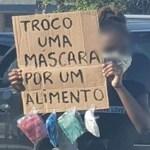 """Foto de menina portando cartaz com a frase """"troco uma máscara por um alimento"""" viraliza nas redes sociais"""