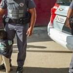 Menino abraça policial depois que mãe recebeu cesta básica, em São Paulo