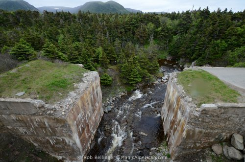 A brook babbles through the rust-stained abutments of a former brige, with pine trees and mountains in the background. Southwest Newfoundland.