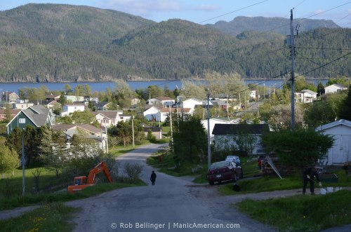 A lone, silhouetted figure walks down a winding road lined by houses, with a fjord and tree-lined mountains in the background. Bonne Bay, Newfoundland.