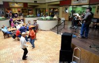 Two older women dance to the music of a band playing in front of stores in a mall while others eat lunch in the background