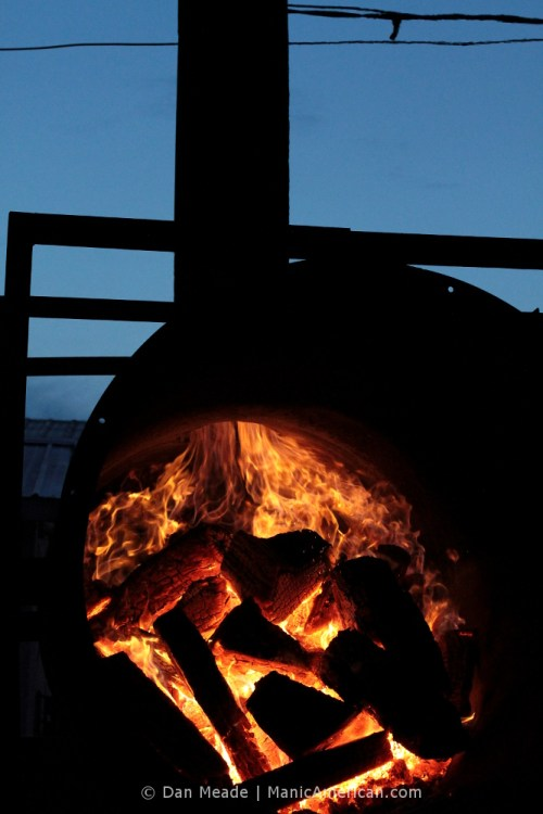 A close-up of of wood burning inside Roy's Inferno, generating coals for making Kentucky barbecue.