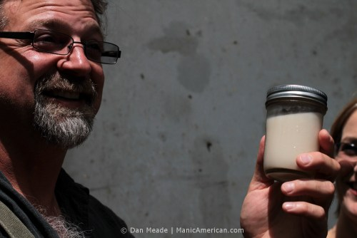 Wes Berry holds up a jar of homemade Korean-style rice wine.