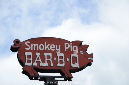 A metal sign in the shape of a pig reads Smokey Pig Bar-B-Q
