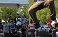 A skater performs a trick before a crowd.