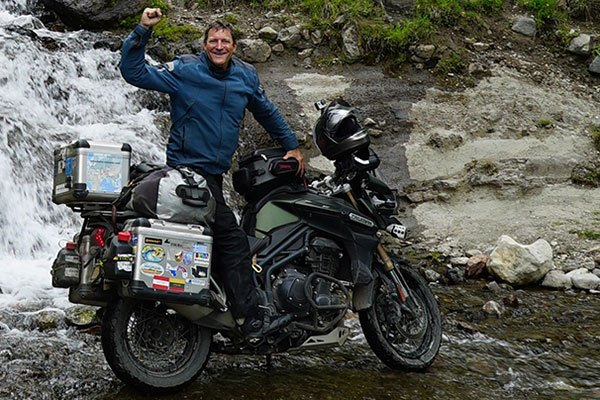Nomad Dave on his motorcycle in a river