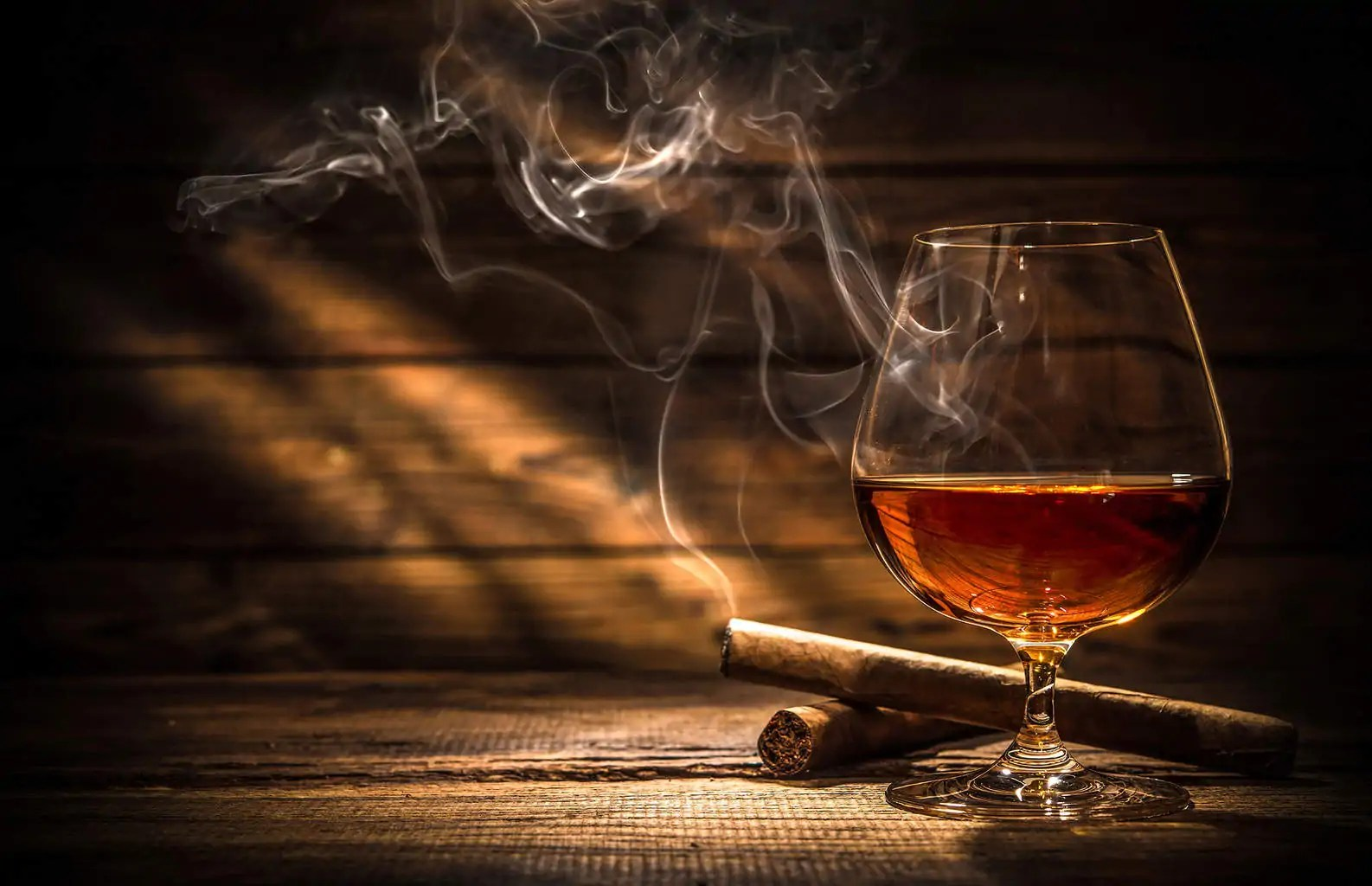 Glass of whiskey with smoking cigar and ice cubes on wooden tabl