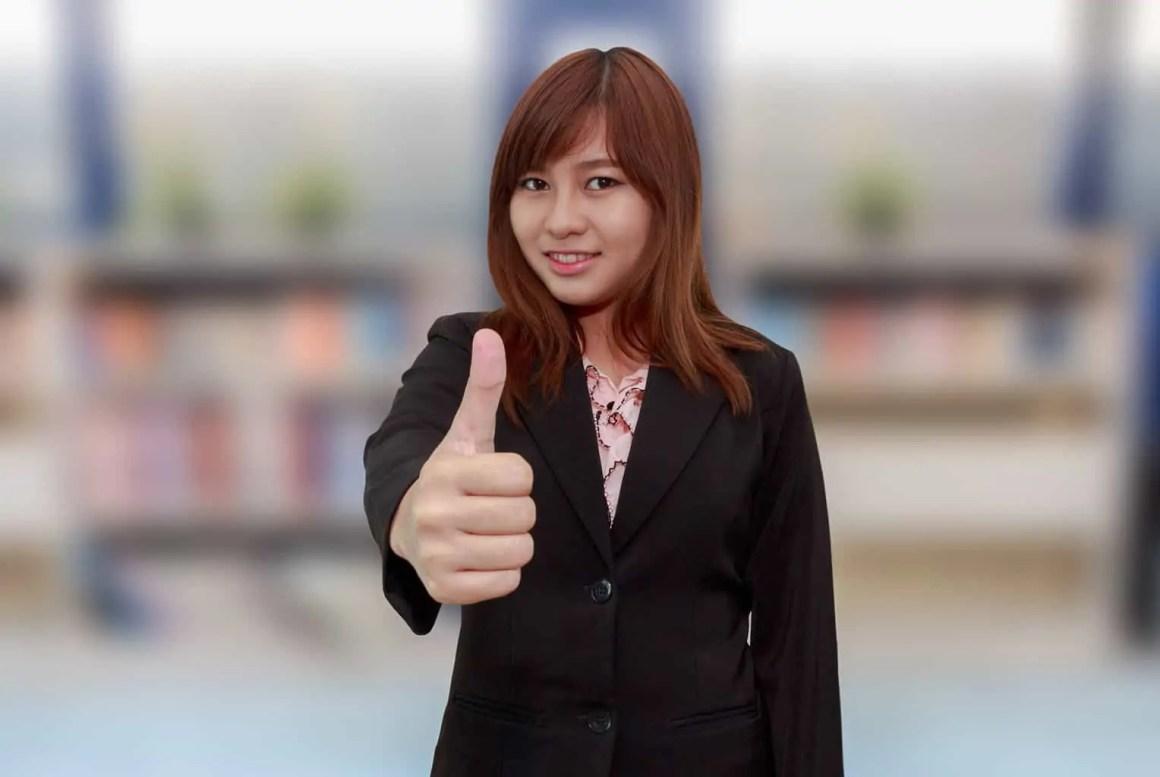 Aziatische dame met haar duim in de lucht