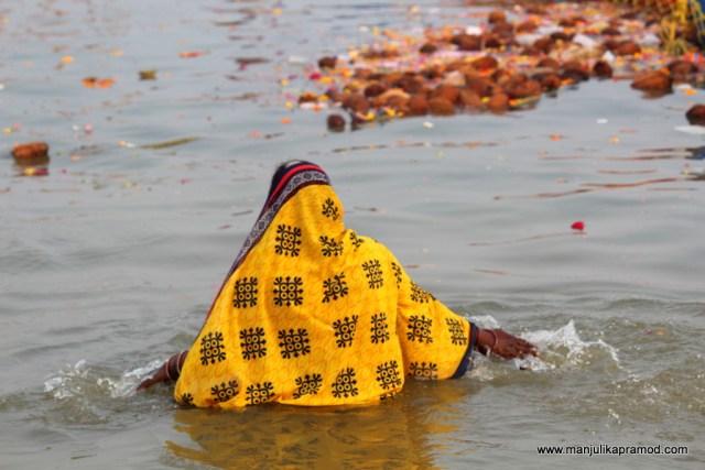 A woman taking a dip at Sangam
