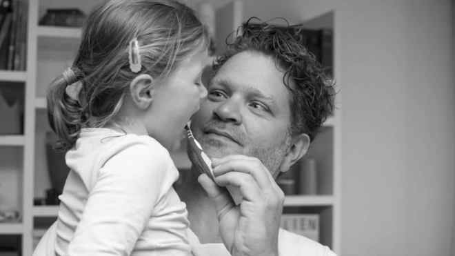 Kind putzt Zähne mit Papa