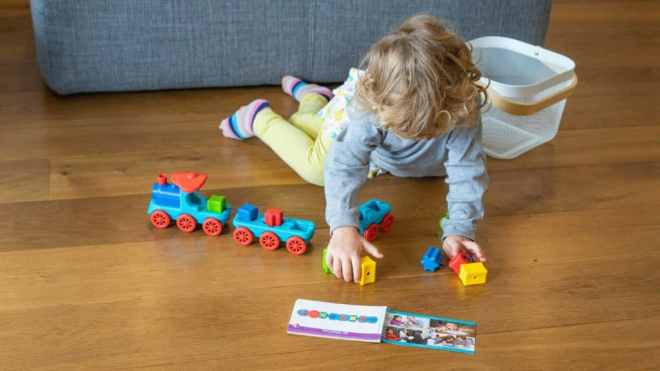 Kind sortiert die Spielsteine der Logik-Lok Lili auf dem Fußboden