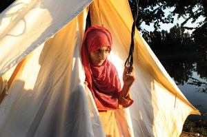 A Kashmiri flood victim at the entrance of a makeshift tent on the outskirts of Srinagar