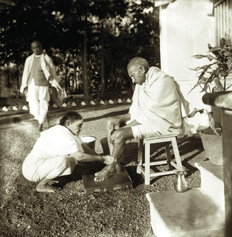 Kasturba washing Mahatma Gandhi's feet with Sardar Patel in the background, Bardoli