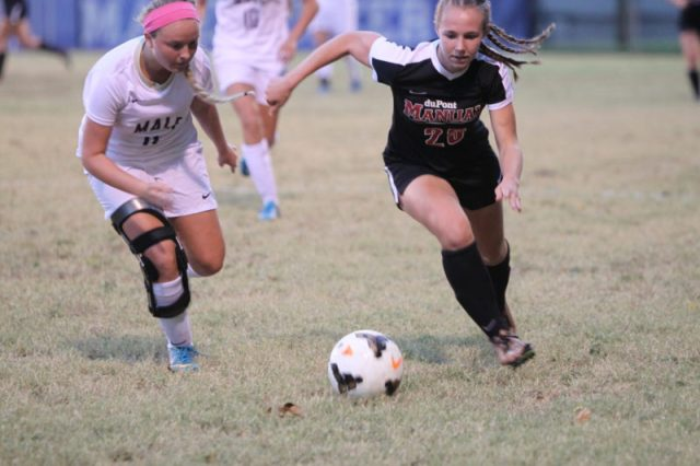 Junior Izzie Zamborini running the ball down the field with a Male player defender her.