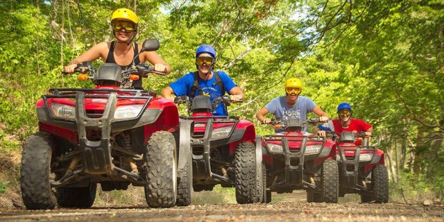 Group riding ATVs through the jungle