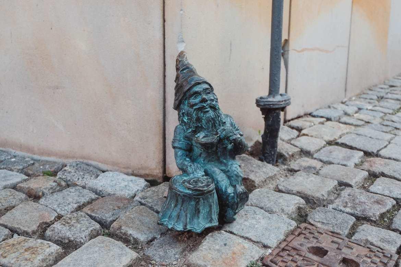 dwarf eating beside a bistro in wroclaw, poland