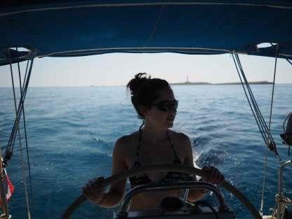 Anaïs à la barre depuis l'île de l'Aire, naviguant le long de la côte sud de Minorque.