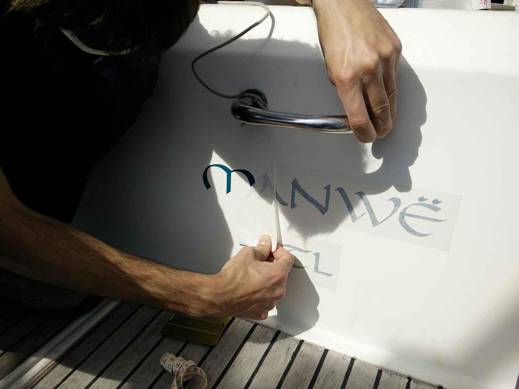 Damien décolle la protection du nouveau nom du bateau.
