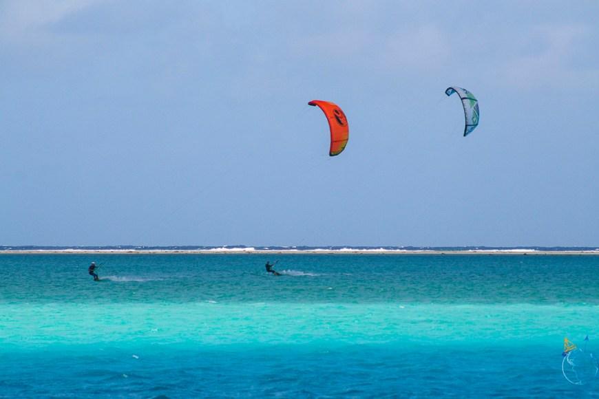 Kitesurf à deux sur le lagon, aile rouge et aile bleue.