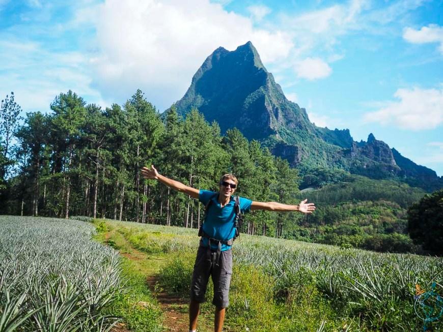 Damien posant dans les champs d'ananas, devant le mont Rotui.