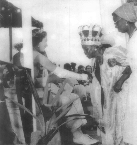 Elizabeth II, Queen of the United Kingdom, greeted by Wokie, Queen of the Vai, wearing the Massaquoi Crown Jewels