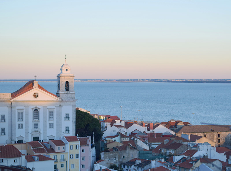 Late afternoon sun hitting the pretty pastel buildings of Lisbon's Alfama neighborhood
