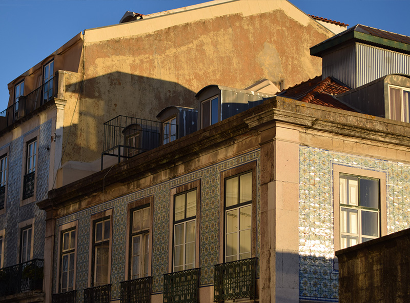 Late afternoon sun is hitting the ceramic tiles of a Lisbon building