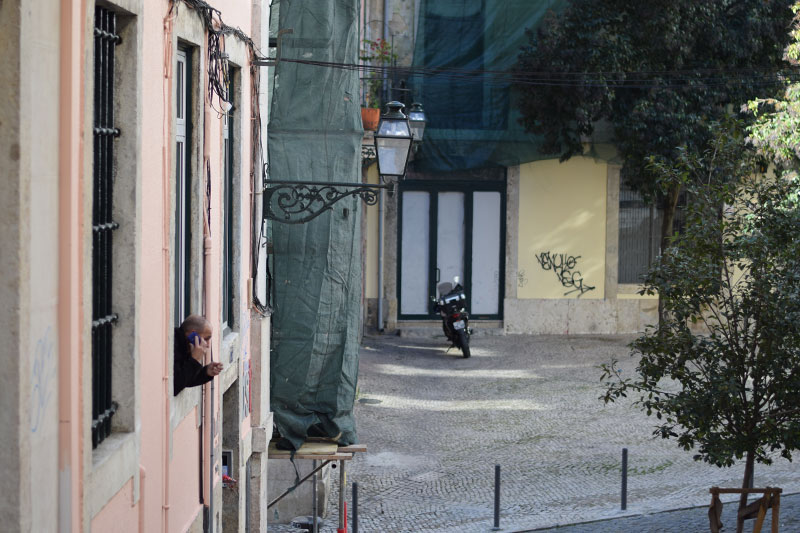 Man in Lisbon leaning out his window talking on the phone
