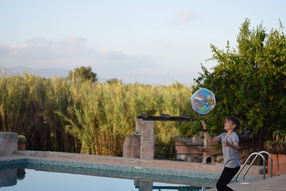 Photo of a boy playing with a ball near a pool in Mallorca Spain