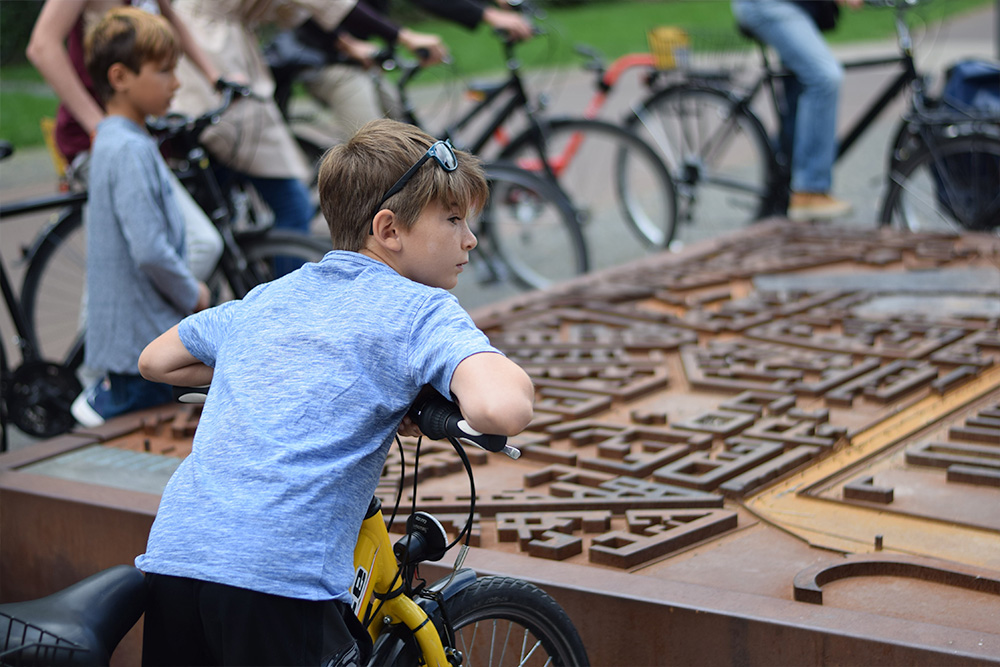 Photo of a boy looking at a map of old Berlin and the Berlin Wall while on a bicycle tour with Berlin on Bike.