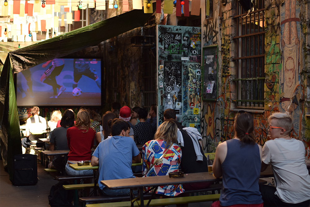 photo of a group of people watching a soccer game on a screen at a Berlin cafe.