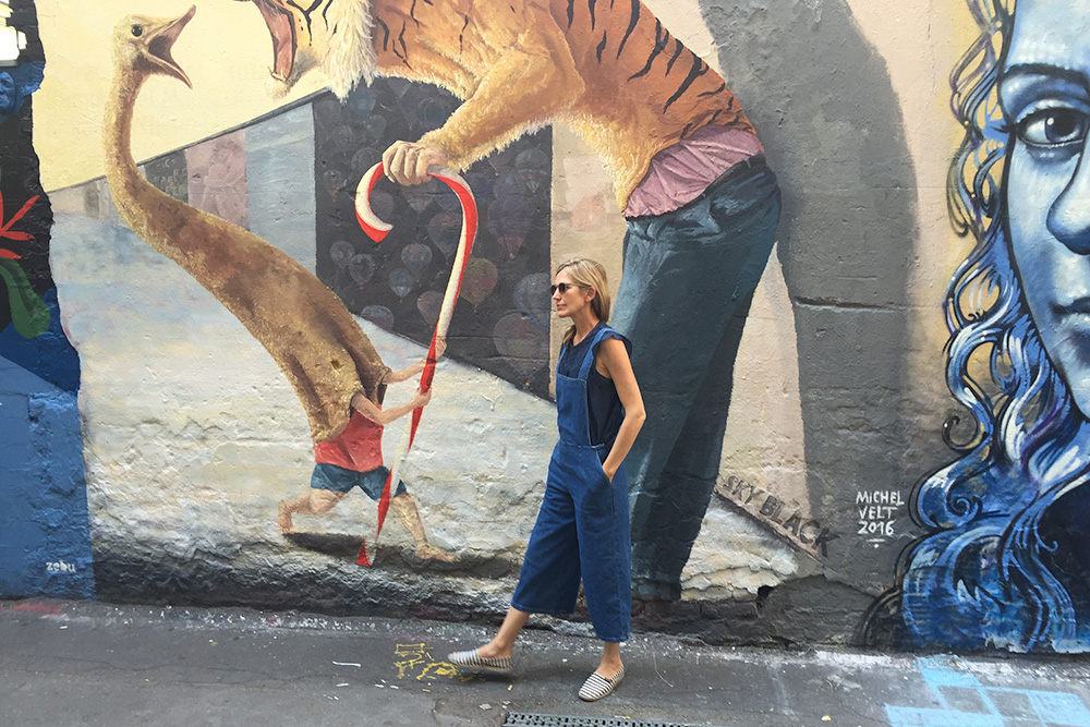 Photo of a woman standing in front of a wall of street art in Berlin.