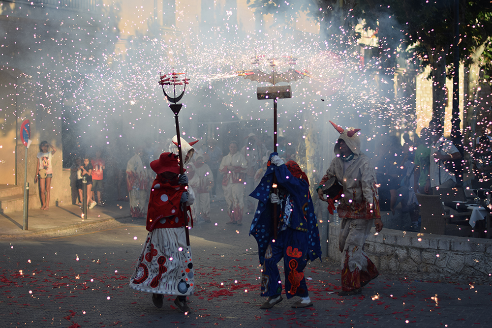 A traditional festival in the streets of Alaro, Mallorca with glimmering firecrackers and children dressed up like devils.