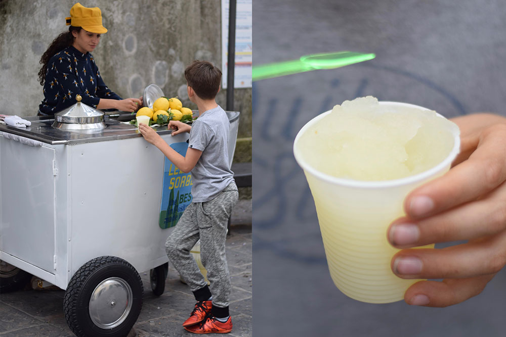 Photo of a boy buying fresh iced lemonade from a seller in Positano, Italy.
