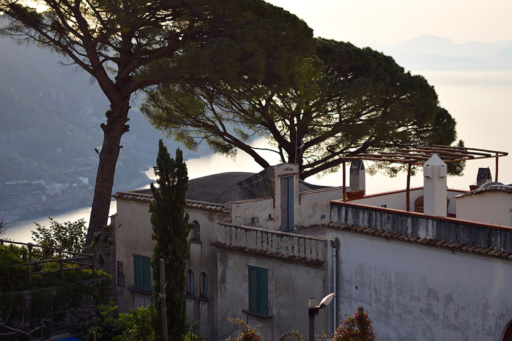 Photo of a beautiful old building surrounded by trees and the Mediterranean Sea in the background in Ravello, Italy.
