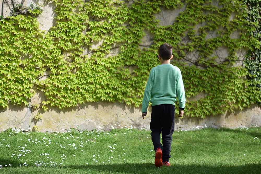Photo of a boy walking in a garden at Villa Cimbrone in Ravello, Italy.