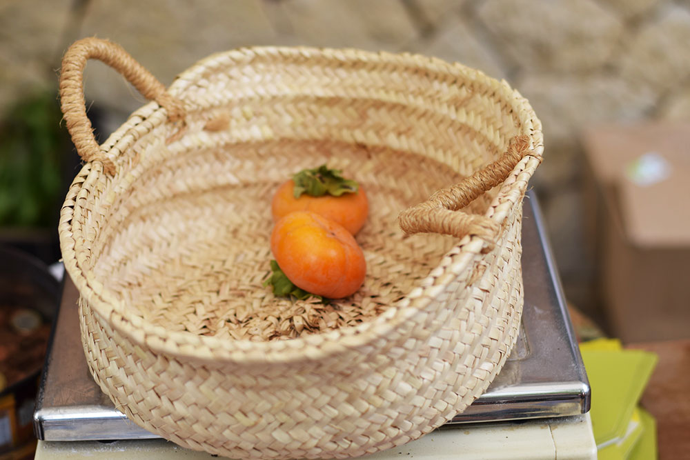 Photograph of two ripe persimmon fruits in a basket at the Santa Maria market in Mallorca, Spain.