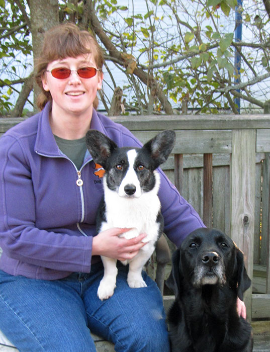Katrin sitting with her two dogs, Zora a corgi and Tom a black retriever mix