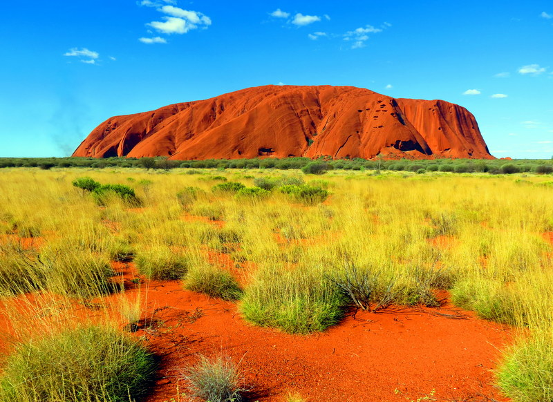 The iconic landmark of Australia's Red Center, the sacred Uluru stands tall as a single rock above a flat arid land.