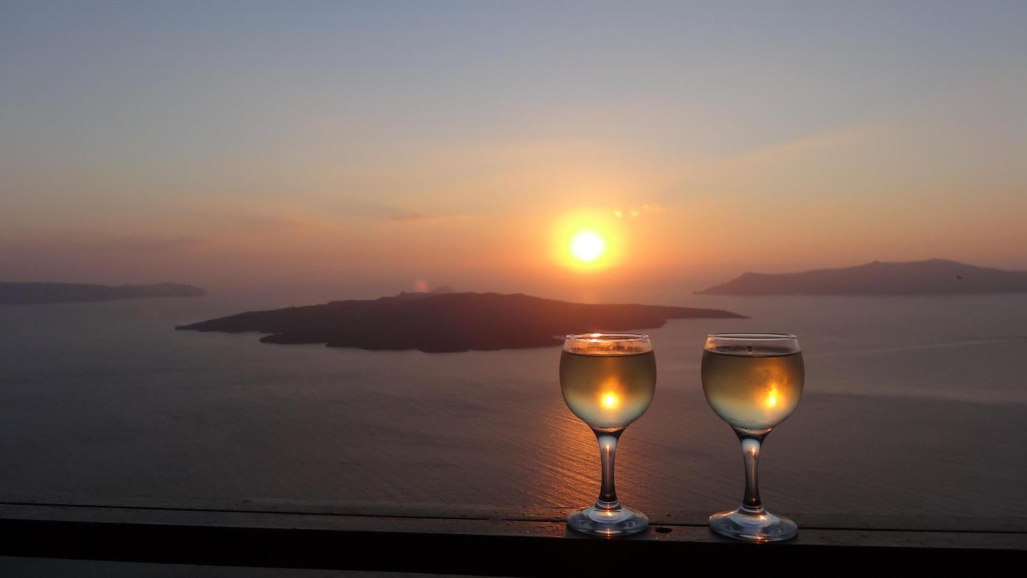 Rest and relaxation. Enjoying a drink on the Santorini caldera during sunset.