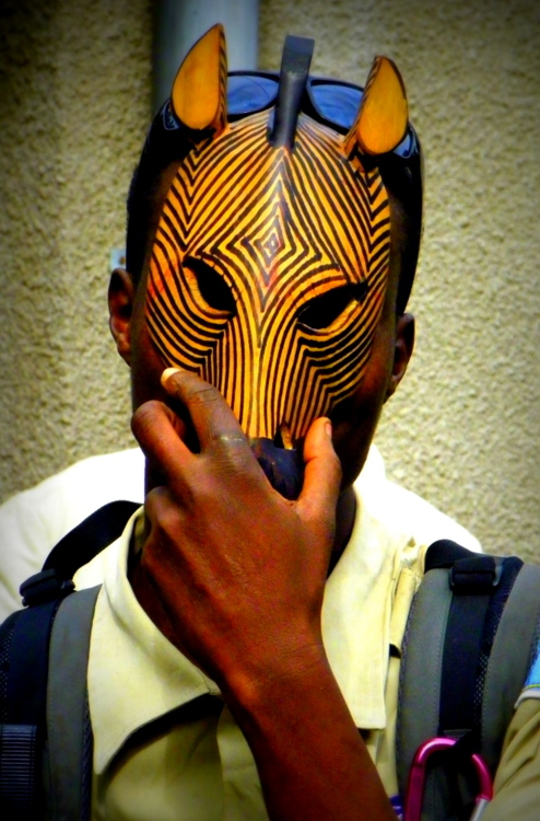 African man holds traditional mask to face.