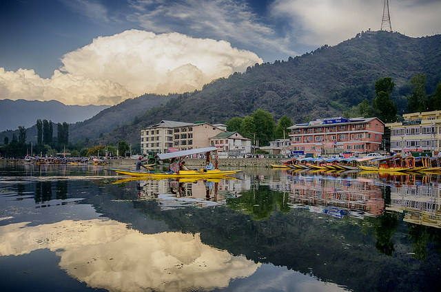 Dal is a vast sheet of water reflecting the carved wooden balconies of houseboats and the misty peaks of the Pir Panjal mountains.