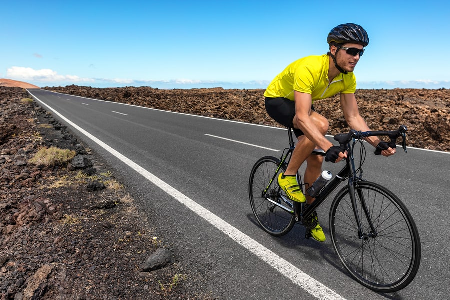 Simple Ways to Improve Bike Aerodynamics Road bike cyclist man biking riding racing bicycle training for triathlon race. Sports athlete biking on road working out cardio living active and healthy lifestyle.