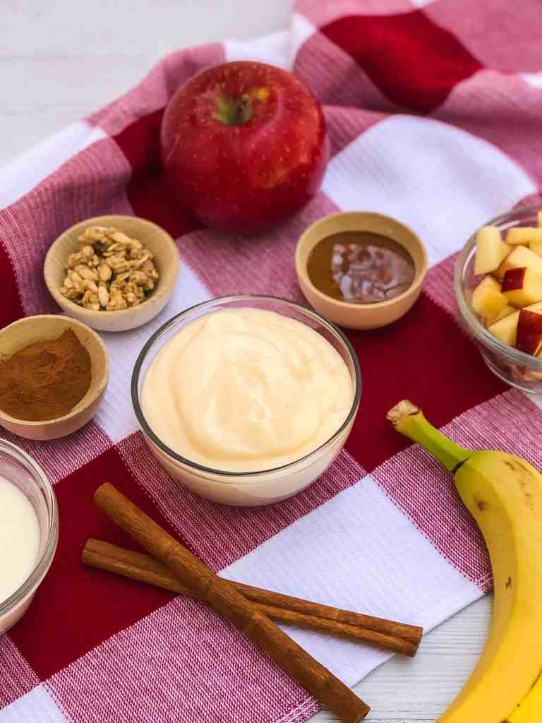 Cinnamon apple banana smoothie bowl ingredients on a red and white checked kitchen towel.