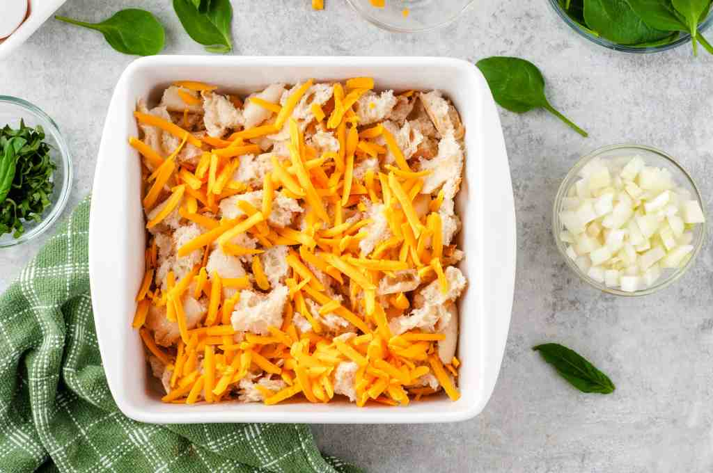 Bread and shredded cheese in a white dish.
