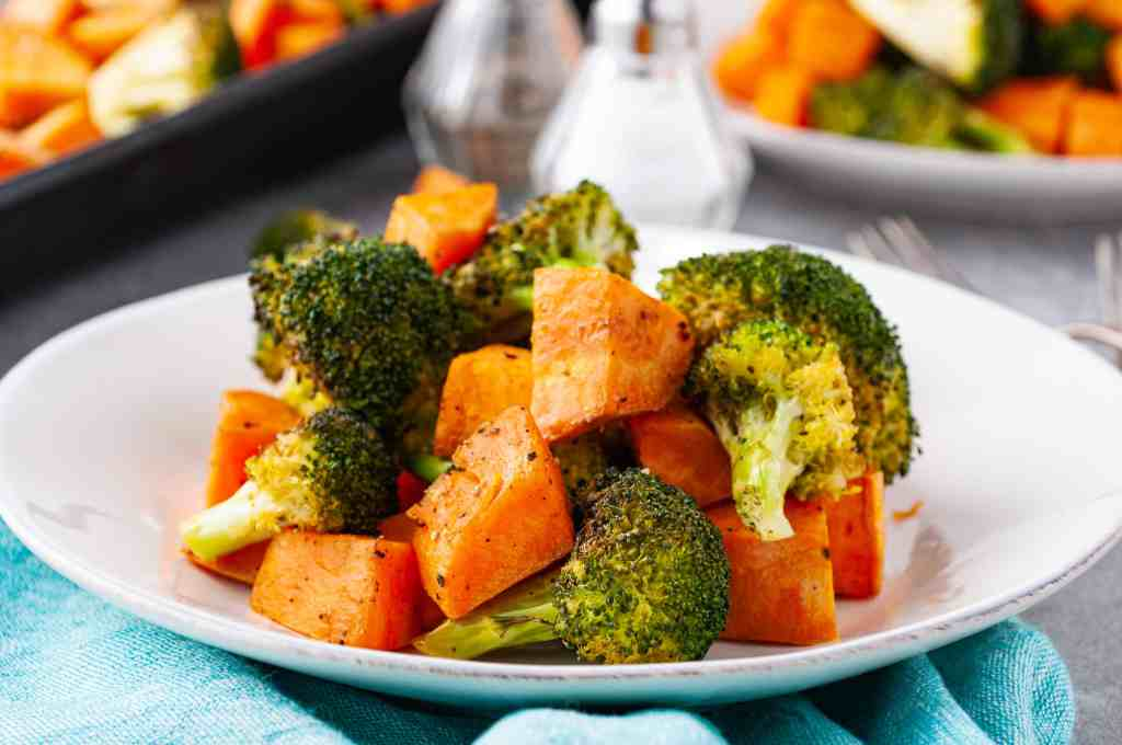 Roasted broccoli and sweet potatoes in coconut oil on a white plate.