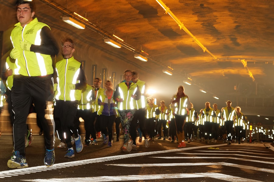 Large group of runners wearing neon yellow reflective vests