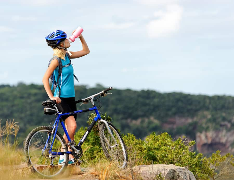 Attractive, healthy woman drinks from her water bottle on mountain bike. active outdoor lifestyle concept